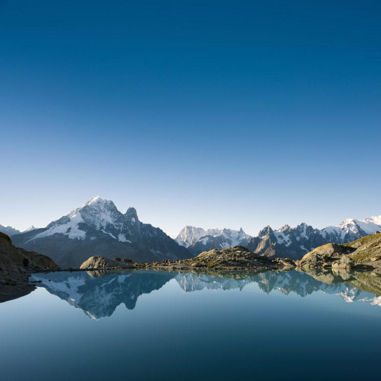 Tranquil scene of Mont Blanc massif reflected in Blanc lake's still water with clear blue sky above